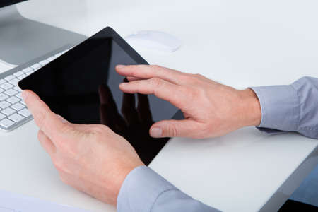 Close-up Of Businessman Using Digital Tablet At Desk photo