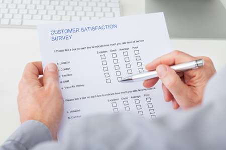 Close-up Of Mans Hand Filling Customer Survey Form