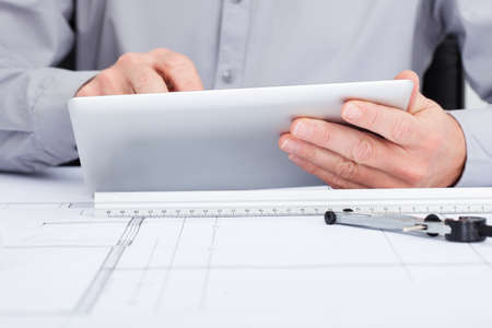 Close-up Of Architect Using Digital Tablet  Over Blueprint photo