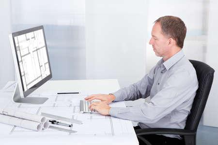 ingeniero civil: Retrato del arquitecto maduro usando la computadora en el escritorio de oficina