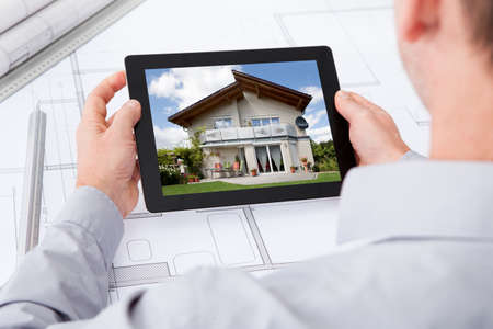 Architect Holding Digital Tablet Over Blueprint Browsing Pictures Of House photo