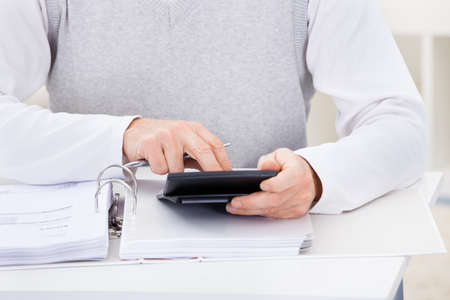 Close-up Of Man Sitting At Home Holding Calculator And Bills Stock Photo - 25349836