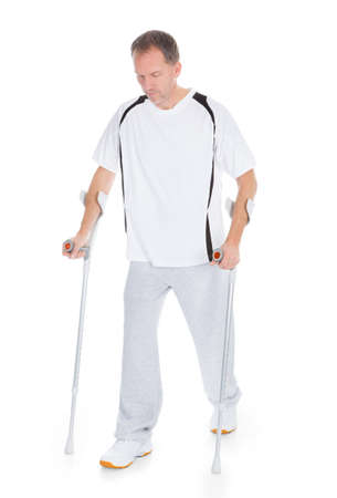 broken leg: Portrait Of A Mature Man With Crutches Isolated Over White Background
