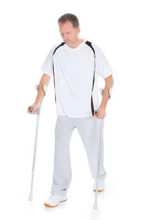 pierna rota: Retrato de un hombre maduro con muletas aislados sobre fondo blanco