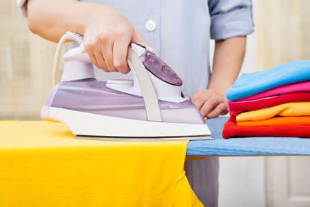 Close-up Of Maid Ironing Clothes On Ironing Board Фото со стока