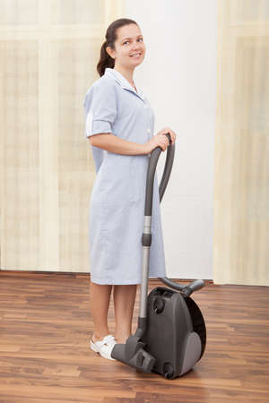 hoover: Young Maid Cleaning Floor With Handheld Vacuum Cleaner