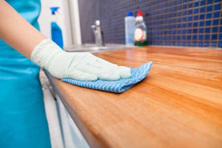 profesionálové: Detailní záběr na mladé ženy nosí Zástěra čištění kuchyňské pracovní desky Reklamní fotografie