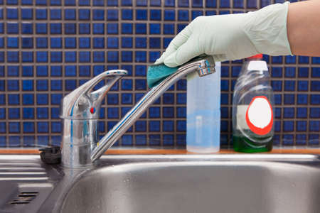 handglove: Close-up Of A Woman Wearing Apron Cleaning Kitchen Faucet Stock Photo