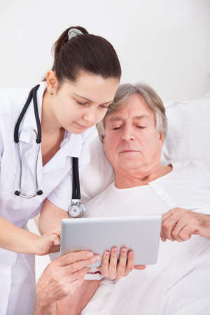 Young Female Doctor Showing Digital Tablet To Senior Patient photo