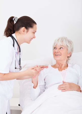 Happy Young Female Doctor With Hand On Senior Female Patient photo