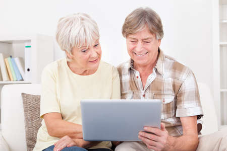 silver surfer: Portrait Of Happy Senior Couple Sitting On Couch Using Laptop