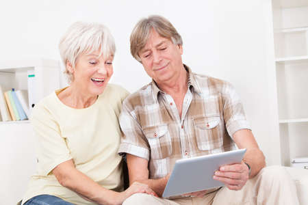 Happy Senior Couple With Digital Tablet Surfing On The Internet At Home photo