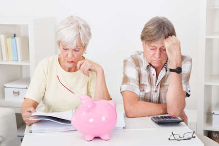 savings problems: Portrait Of Upset Senior Couple Calculating Finance At Home