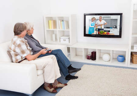 watching movie: Senior Couple Watching Television Showing Recipe At Home