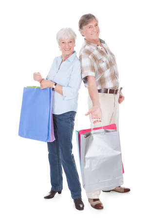 Happy Senior Couple Holding Shopping Bag Over White Background photo