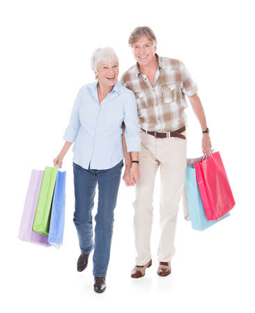 Happy Seniors Couple Walking With Shopping Bag Over White Background photo