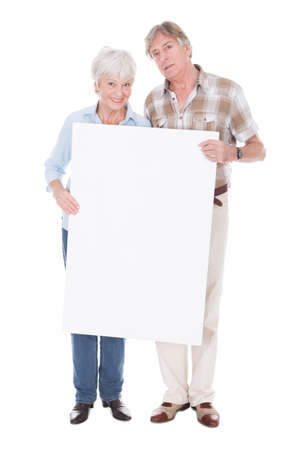 Senior Lovely Couple Holding Together A Blank White Board Over White Background photo