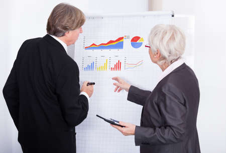 Mature Businessman And Businesswoman Discussing About Graph Shown On Flipchart photo