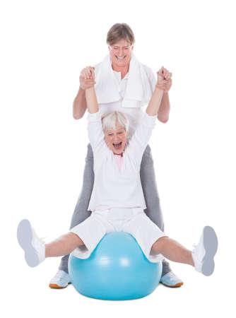 Happy Senior Couple Exercising With Pilates Ball On White Background photo