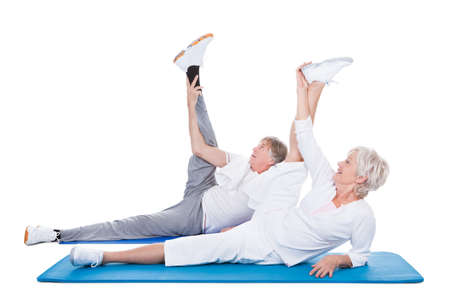 Happy Senior Couple Doing Exercise On Blue Exercise Mat