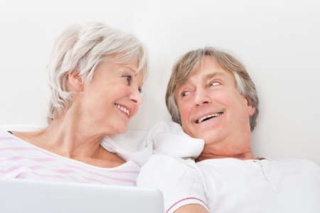 Portrait Of Loving Senior Couple Lying On Bed photo