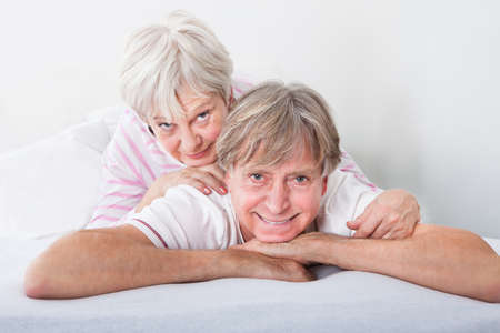 Happy Senior Couple Relaxing On Sofa At Home photo