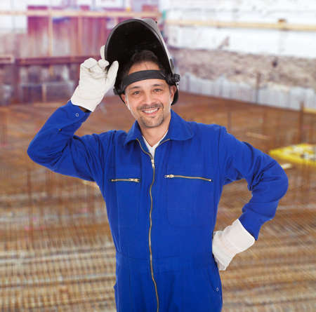 Portrait Of Confident Welder Holding Welding Mask photo