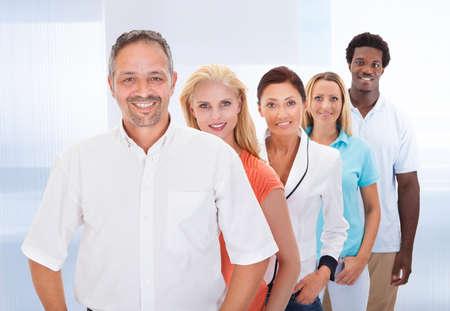 Groep Gelukkige multiraciale mensen staan in een rij Stockfoto