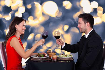 gourmet dinner: Pareja joven feliz que sacude el vino en el restaurante
