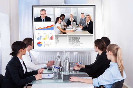 online conference: Businesspeople Sitting In A Conference Room Looking At Screen