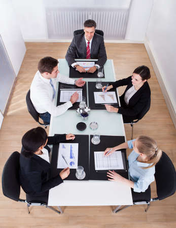 High Angle View Of Businesspeople Sitting In Conference At Office Desk photo