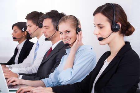 Businesspeople In A Row Wearing Headset Working At Office photo