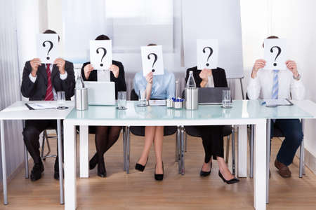 Businesspeople Sitting In Conference Room Holding Question Mark In Front Of Face photo
