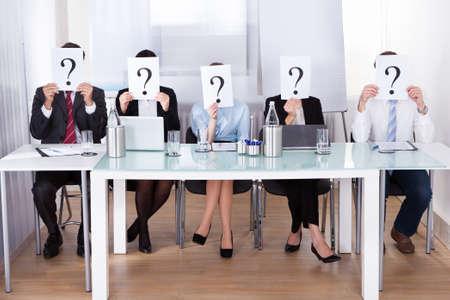 Los empresarios se sientan en la Sala de Conferencias de la explotación agrícola del signo de interrogación delante de la cara Foto de archivo - 25535509
