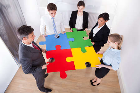 High Angle View Of Businesspeople Holding Multi Colored Jigsaw Puzzle photo