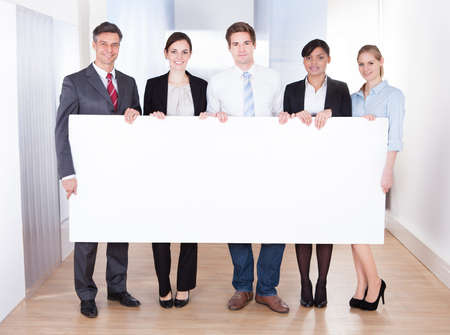 Group Of Happy Businesspeople Holding Blank Placard photo