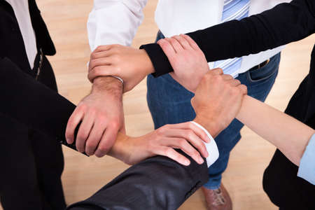 commitment: High Angle View Of Businesspeople Holding Wrist