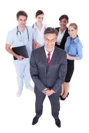 Happy Businessman Standing In Front Of  Professional Workers Over White Background photo