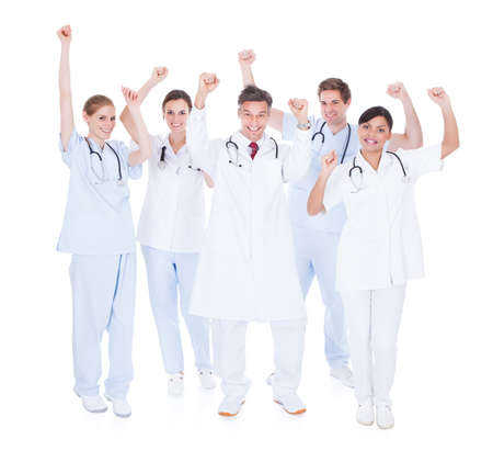 Happy Group Of Doctors Raising Hand Over White Background photo