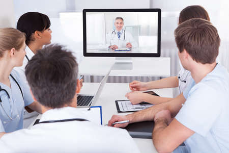 Group Of Doctors Looking At Online Presentation On Computer In Hospital