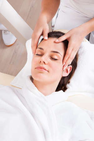 Portrait Of Young Beautiful Woman Receiving Head Massage At Spa photo