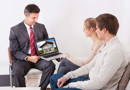 Estate Agent Showing House On Laptop To Young Couple Sitting At Home photo