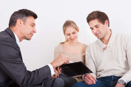 counseling: Male Consultant Showing Clipboard To Happy Young Couple Stock Photo