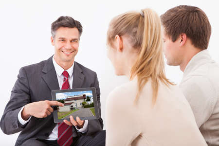property agent: Happy Estate Agent Showing House On Tablet Pc To Couple At Home