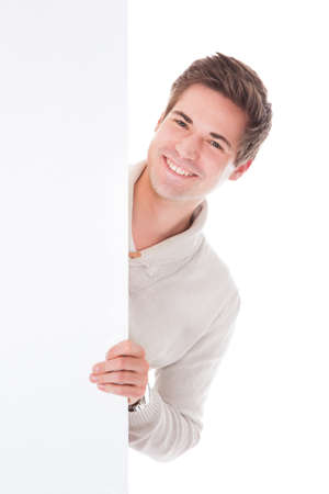 Young Man Looking From Behind The Blank Banner Over White Background photo