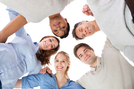 Happy Group Of People In Circle Looking Down Over White Background