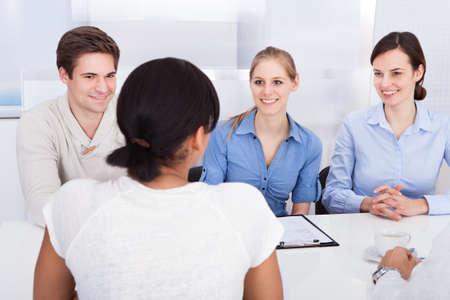 comité d entreprise: Les jeunes gens d'affaires heureux de parler entre eux dans le bureau Banque d'images