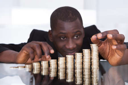conservacion del agua: Retrato de un hombre de negocios africano joven apilar monedas Fila En El Escritorio Foto de archivo