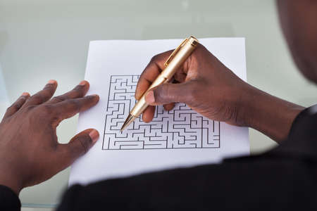 Close-up Of A Businessman Looking At Maze Puzzle Holding Pen photo