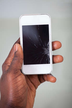 Close-up Of A Businesspersons Hand Holding Cellphone With Cracked Screen photo